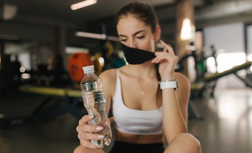 Devojka pije vodu za vreme vežbanja